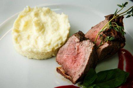 Photo pour Vue macro sur plat finement décoré de morceaux de viande cuits au four servis avec de la purée de pommes de terre garniture et sauce rouge sur assiette de restaurant blanc - image libre de droit