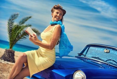 Foto de Hermosa mujer feliz leyendo un libro cerca coche cabriolet retro en la playa. Paisaje idílico - Imagen libre de derechos