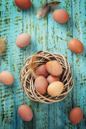 Photo for Chicken eggs in a nest on a wooden background - Royalty Free Image