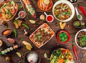 Různé asijské jídlo na rustikální pozadí, pohled shora, místo pro text