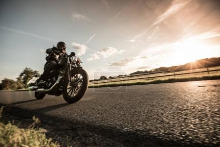Photo pour Homme à moto sportive à la campagne pendant le coucher du soleil . - image libre de droit