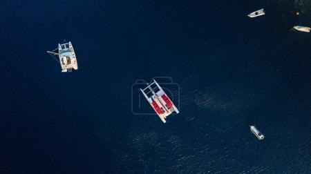 Boats and catamarans in deep blue water, Santorini, Greece.
