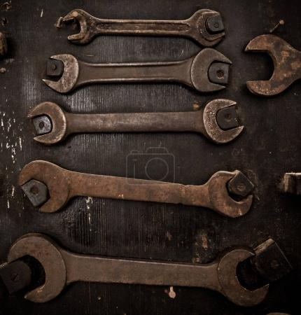 Dirty set of hand tools on a wooden background.