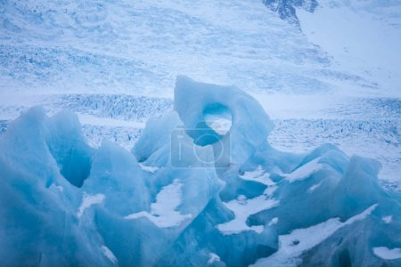 Icebergs swimming on frozen water, close-up.