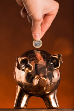 Hand putting coin money to piggy bank saving.