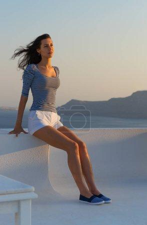Santorini travel tourist brunette woman visiting famous white Oia village.