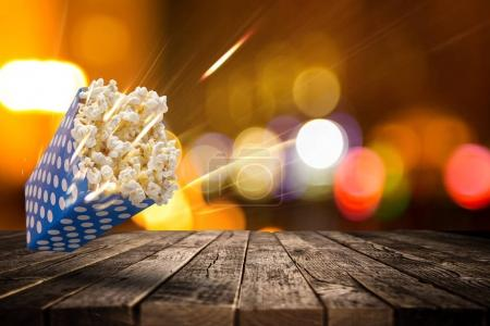 Paper box of popcorn on old wooden table.