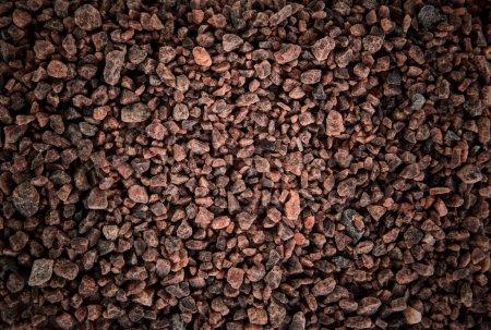 Dark brown coarse grain salt heap texture.
