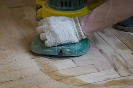 Worker polishing old wooden parquet floor with grinding machine