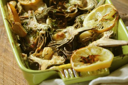 fried artichokes with garlic and lemon on pan on rustic table