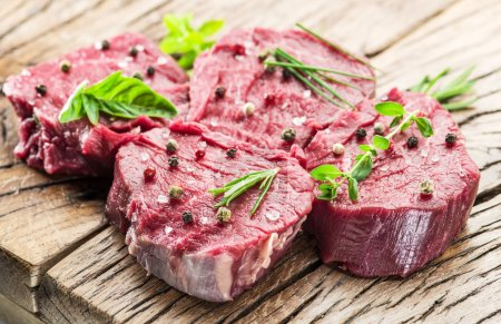 Photo for Pieces of beef tenderloin on the wooden cutting board. - Royalty Free Image