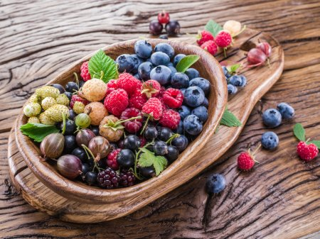 Photo for Ripe berries in the wooden bowl on the table. - Royalty Free Image