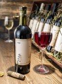Sklenka vína a vinných lahví