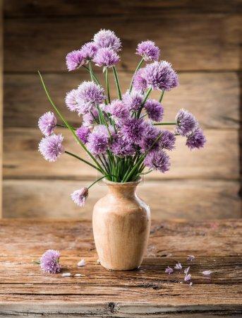 Photo pour Bouquet de fleurs d'oignon (ciboulette) dans le vase sur la table en bois . - image libre de droit