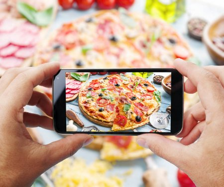 Photo for Taking photo of pizza by smartphone. Closeup view of  process. File contains clipping paths for smartphone and it's picture. - Royalty Free Image