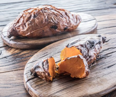 Baked batata on the old wooden table.