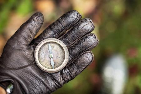 Man's hand in a leather glove holding a compass. Nature backgrou