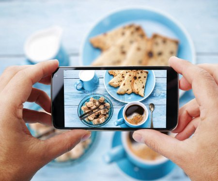 Taking photo of one's breakfast with cup of coffe by smartphone.
