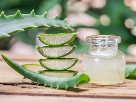 Fresh aloe leaves and aloe gel in the cosmetic jar on wooden tab