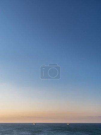 Calm sea and cloudless orange evening sky.