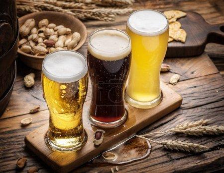 Verres de bière et snacks sur la table en bois .