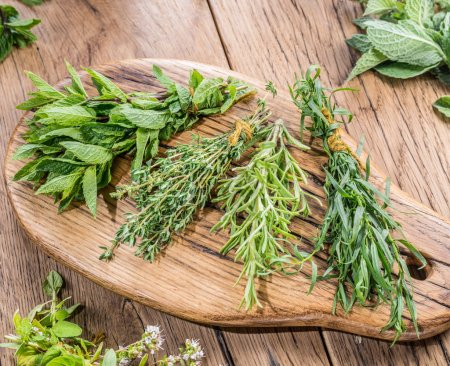 Photo for Different bunches of fresh herbs on the wooden table. - Royalty Free Image