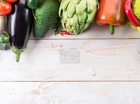 Different colorful vegetables arranged as a frame. Wooden backgr