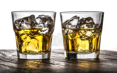 Whiskey glasses or glasses of whiskey with ice cubes on the wood