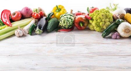 Photo pour Légumes colorés différents disposées comme un cadre. Fond en bois. - image libre de droit