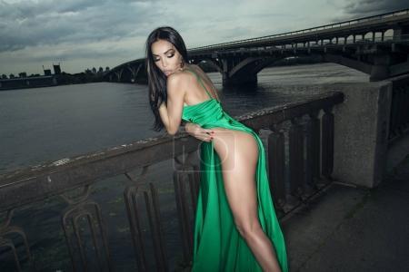 mujer en vestido sexy en la orilla del río
