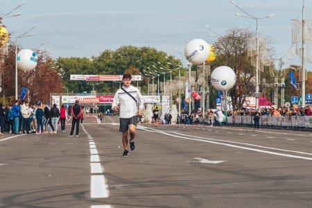 Photo for September 15, 2018 Minsk Belarus Half Marathon Minsk 2019 A man with a bag on his shoulder runs along the road - Royalty Free Image
