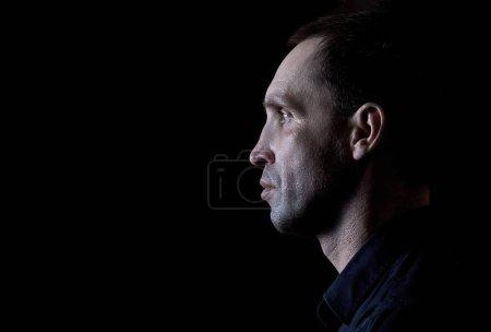 Photo pour Homme sérieux en chemise noire de profil sur fond sombre - image libre de droit