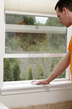 cleaning a window sill with a