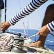 Young handsome sailor pulling rope on sailboat...