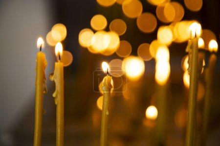 Photo pour Bougie en face de nombreux candleflames défocalisés, créant une atmosphère spirituelle et en souvenir de leurs proches - image libre de droit