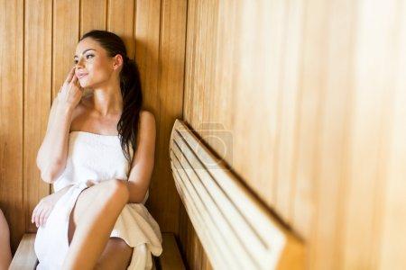 Photo pour Femme assise sur le banc dans le sauna - image libre de droit