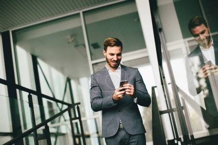 Young modern businessman with smartphone