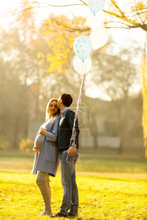 Loving couple with balloons in park