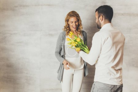 Man giving to girl a bouquet of tulips