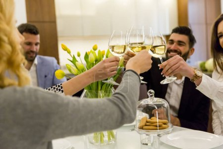 Young friends celebrating with white wine