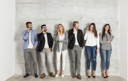 Photo pour Jeunes gens d'affaires avec des téléphones portables debout près du mur - image libre de droit