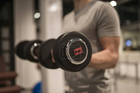 Photo for View at bodybuilder training with dumbbells in the gym - Royalty Free Image