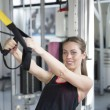 Women doing push ups training arms with trx fitnes...