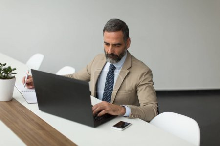 Senior  director sitting at desk and working on laptops in the office