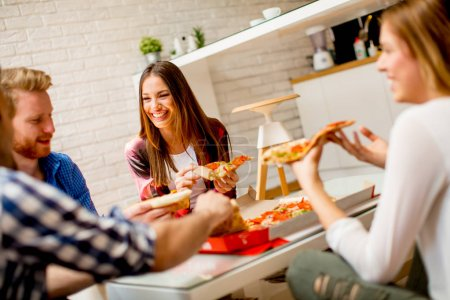 Group of young friends eating pizza at home
