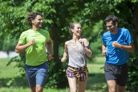 Woman and two young men running in the park at summer