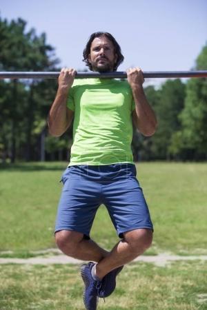 Photo pour Musclé homme faisant pull-ups sur barre horizontale dans le parc - image libre de droit