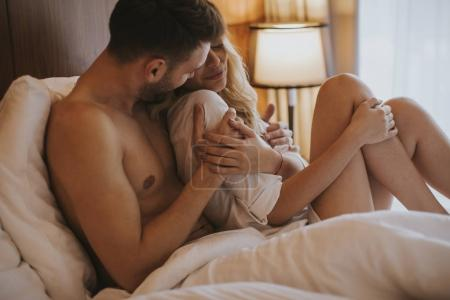 Photo for Loving and hugged couple on the bed in the room - Royalty Free Image