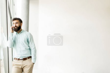 Handsome young man in formalwear talking on the mobile phone in office