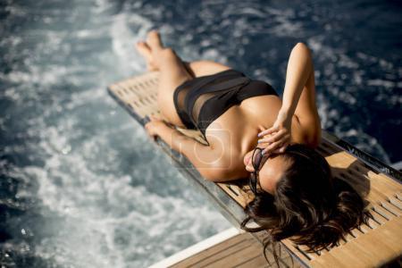 Photo pour Jolie jeune femme se détendre sur le yacht sur la mer à la journée ensoleillée - image libre de droit